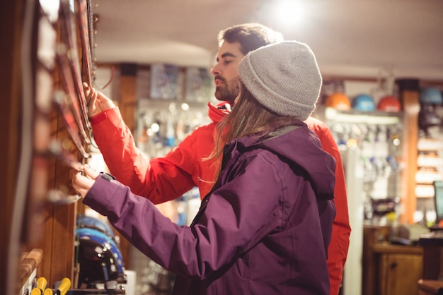 Paar, das skistock in einem geschäft betrachtet Kostenlose Fotos