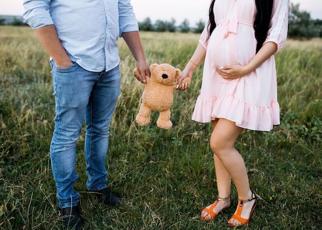 Paar eines mannes und einer schwangeren frau, die ein teddybärspielzeug halten Premium Fotos