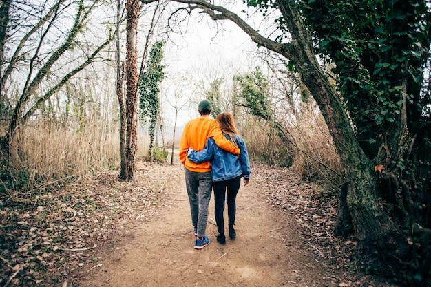 Paar gehen zusammen auf schotterwaldweg Kostenlose Fotos