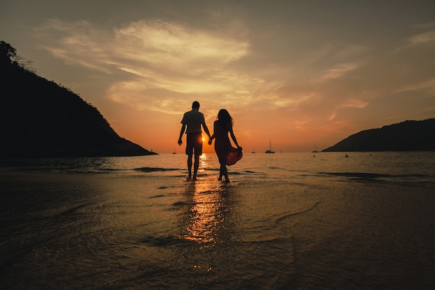 Paar händchen haltend am strand   Premium-Foto