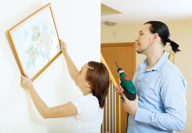 Paar hängt das kunstbild an der wand Kostenlose Fotos
