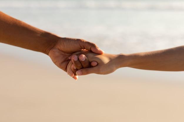 Paar hand in hand voneinander am strand Kostenlose Fotos