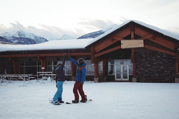 Paar high fiving auf schneebedecktem feld Kostenlose Fotos