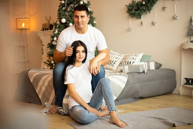 Paar im schlafzimmer mit weihnachtsdekoration. mann umarmt frau. Premium Fotos
