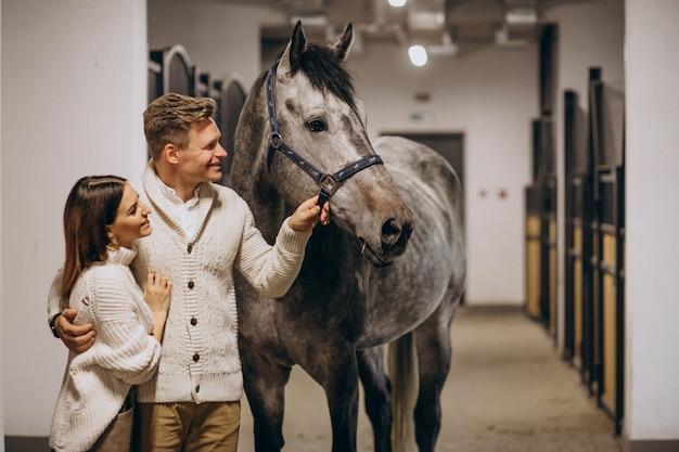 Paar im stall mit pferd Kostenlose Fotos