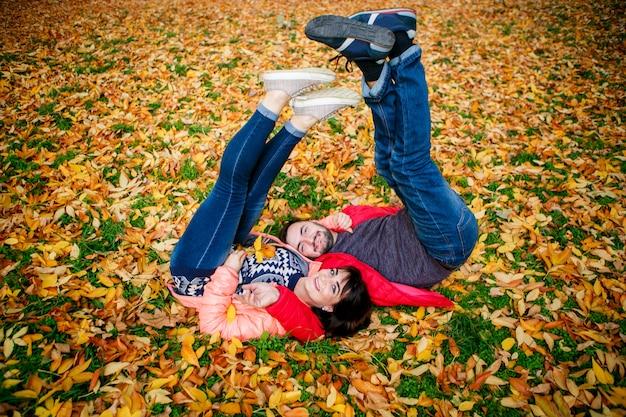 Paar in der liebe ist auf herbstblättern am park entspannend Premium Fotos