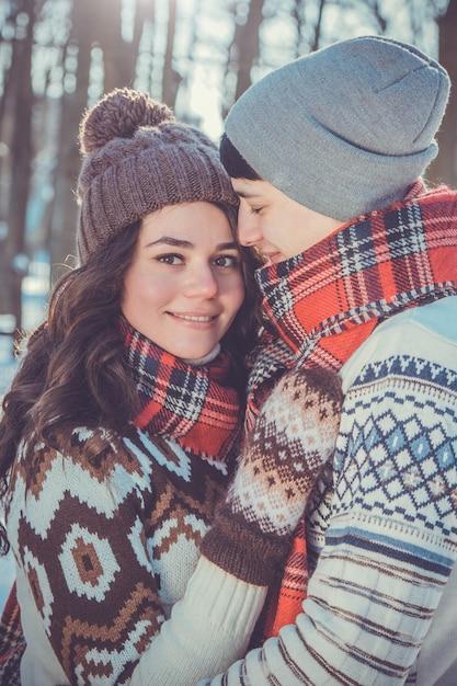 Paar in der liebe umarmt im winterpark Premium Fotos