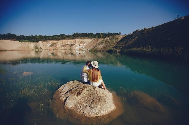Paar in der nähe von blauem wasser Kostenlose Fotos