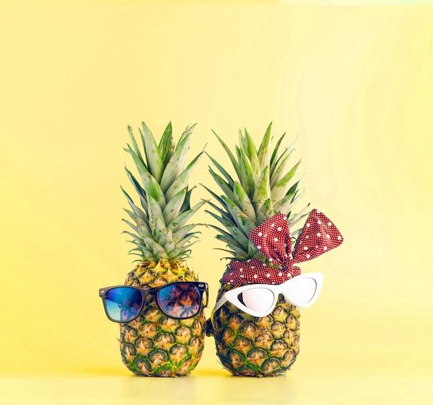 Paar in liebe einkaufen in einem resort im urlaub. ananas mit brille in form eines mannes und eines mädchens auf hellem hintergrund Premium Fotos