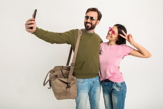 Paar isoliert, hübsche lächelnde frau im rosa t-shirt und mann im sweatshirt mit reisetasche, jeans und sonnenbrille tragend, spaß haben, zusammen reisen und lustiges selfie-foto am telefon machen Kostenlose Fotos
