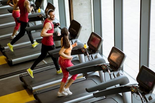 Paar laufen auf laufbändern im fitnessstudio Premium Fotos