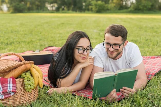 Paar lesung auf einer picknickdecke Kostenlose Fotos