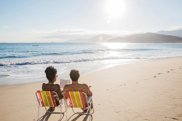 Paar lesung auf liegestühlen am strand Kostenlose Fotos