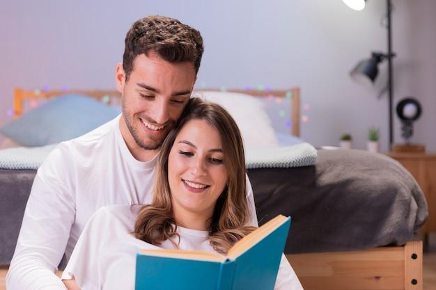 Paar liest in ihrem schlafzimmer Kostenlose Fotos
