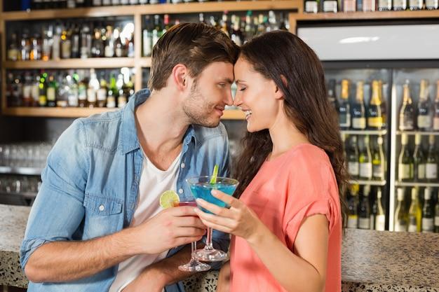 Paar mit cocktails anstoßen Premium Fotos
