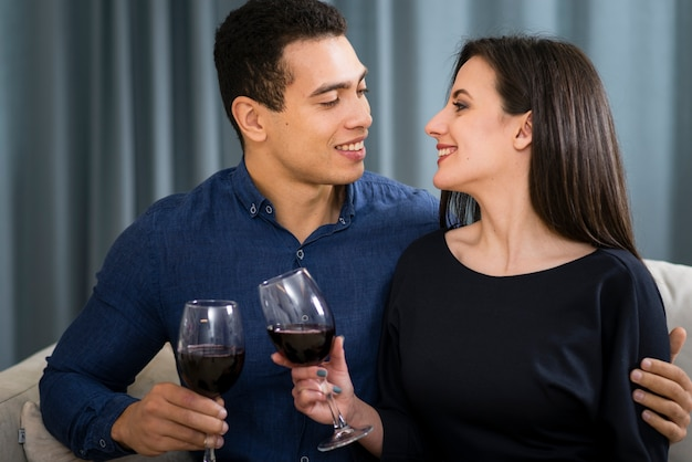 Paar mit einem glas wein beim sitzen auf der couch Kostenlose Fotos