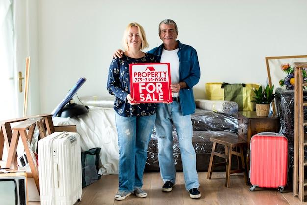 Paar mit einer immobilie zum verkauf zeichen Premium Fotos