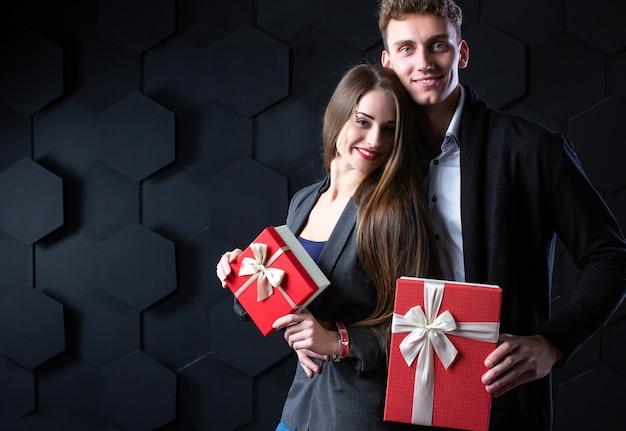 Paar mit geschenken. schöner mann und frau, die geschenkboxen auf einem dunklen hintergrund halten. feier und romantisches konzept. Premium Fotos