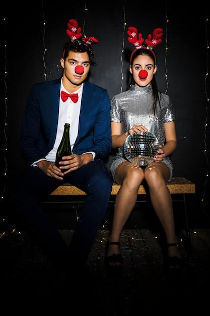 Paar mit hirsch geweih stirnbänder und lustige nasen mit flasche und discokugel Kostenlose Fotos