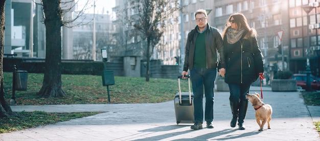Paar mit koffer und hund zu fuß Premium Fotos