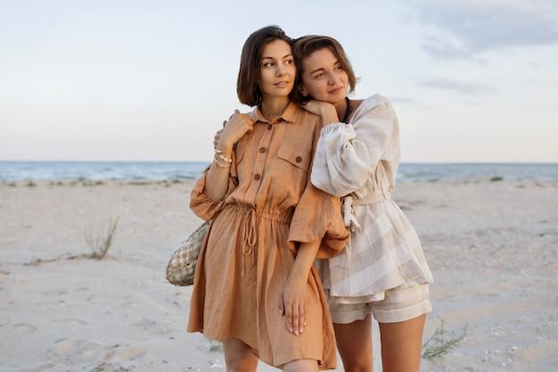 Paar mit kurzer frisur in leinensommerkleidung, die am strand aufwirft Kostenlose Fotos