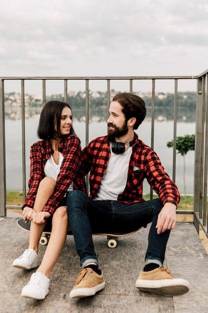Paar mit passenden outfits sitzen Kostenlose Fotos