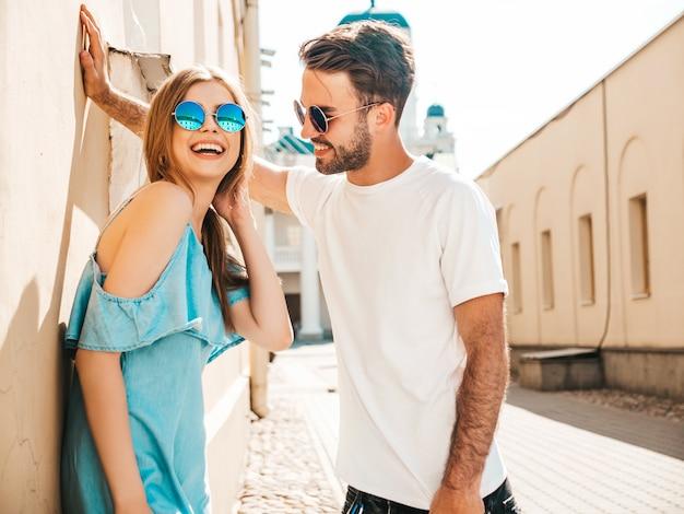 Paar mit sonnenbrille posiert auf der straße Kostenlose Fotos