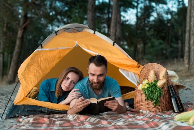 Paar niederlegen und lesen Kostenlose Fotos