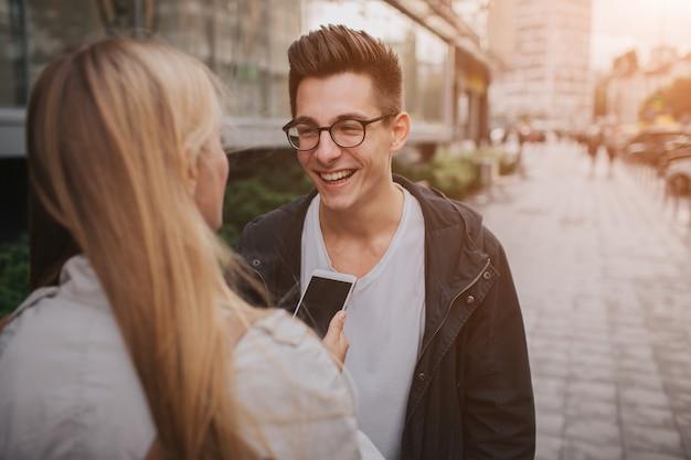 Paar oder freunde, die lustig lachen und spaß mit einem smartphone in einer großstadtstraße haben. Premium Fotos