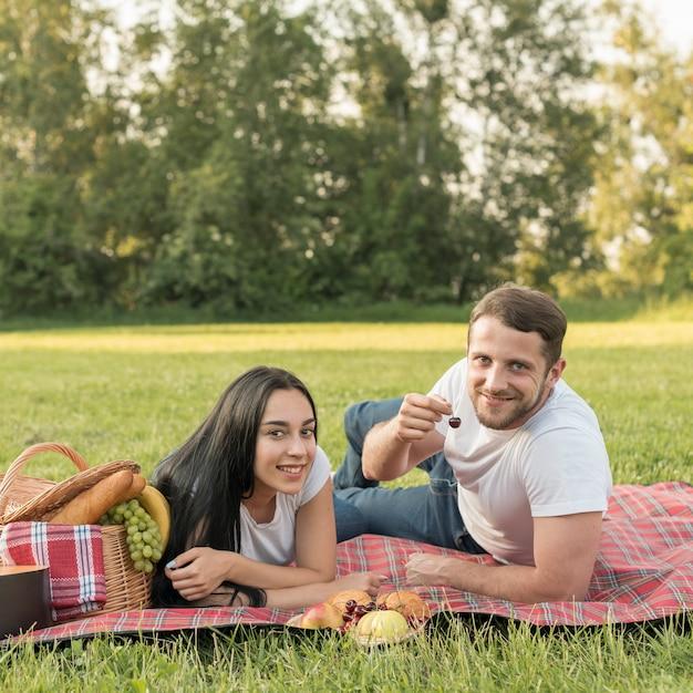 Paar posiert auf einer picknickdecke Kostenlose Fotos