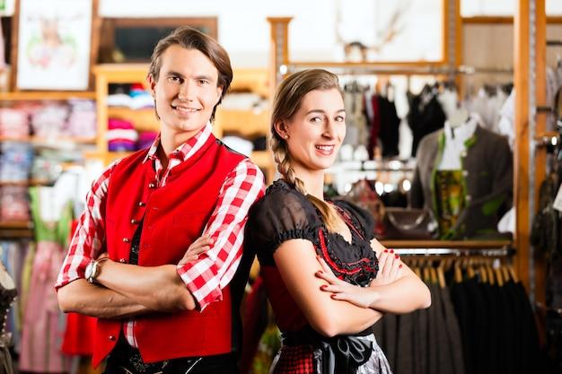 Paar probiert dirndl oder lederhosen in einem laden aus Premium Fotos
