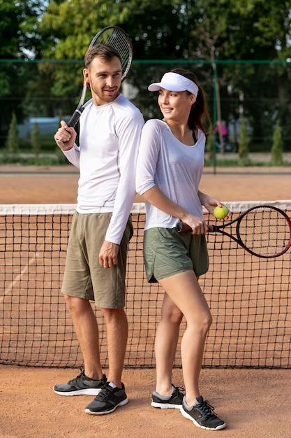 Paar rücken an rücken auf dem tennisplatz Kostenlose Fotos