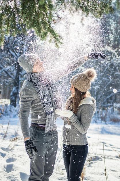 Paar rüttelt tannenzweig mit schnee. leute, die spaß haben Premium Fotos