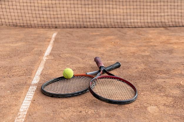 Paar schläger mit tennisball auf dem boden Kostenlose Fotos