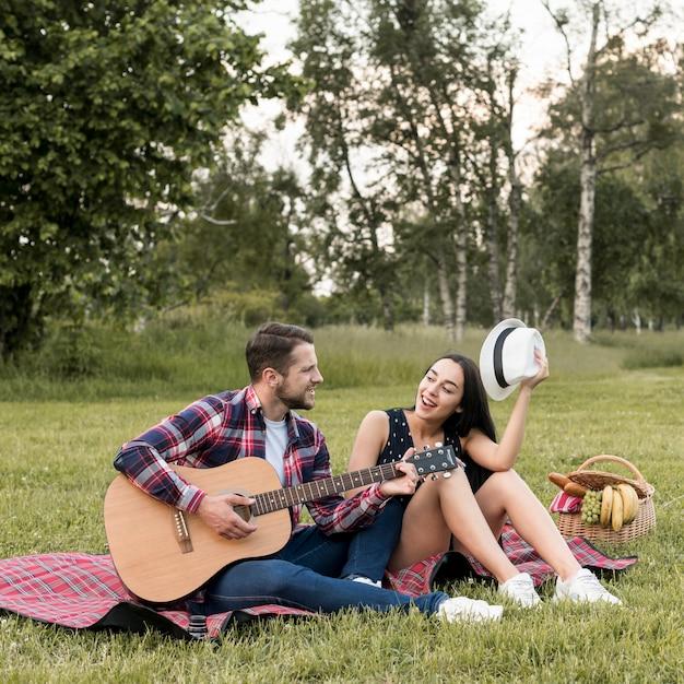 Paar singt auf einer picknickdecke Kostenlose Fotos