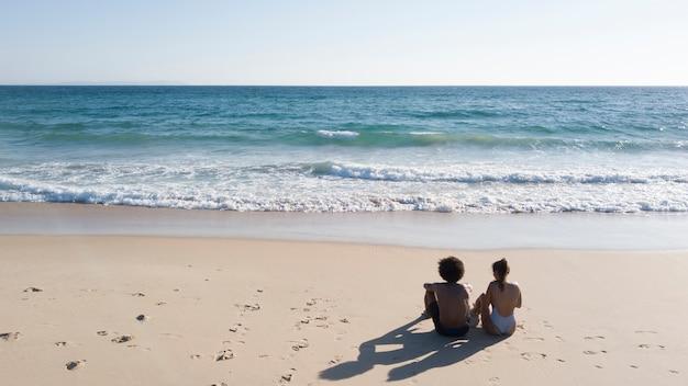 Paar sitzt am sandstrand Kostenlose Fotos