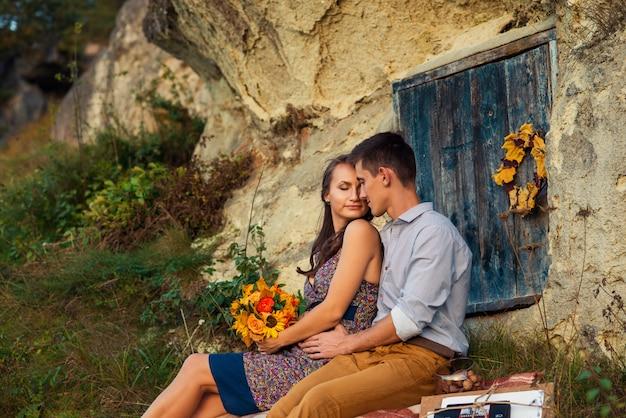Paar sitzt auf dem plaid in der nähe des felsens mit höhlen und blauen holztür. Premium Fotos