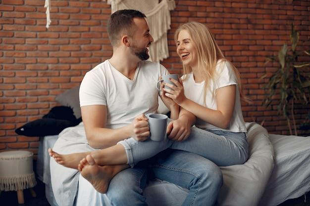 Paar sitzt auf einem bett in einem raum Kostenlose Fotos