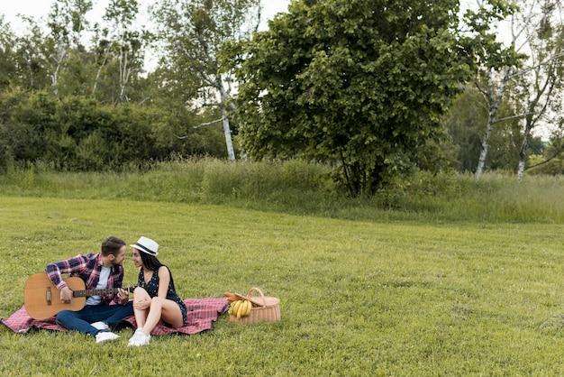 Paar sitzt auf einer picknickdecke Kostenlose Fotos