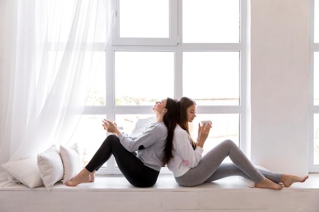 Paar sitzt rücken an rücken neben dem fenster Kostenlose Fotos