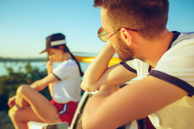 Paar sitzt und ruht am strand am sommertag in der nähe des flusses Kostenlose Fotos