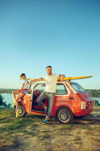 Paar sitzt und ruht am strand an einem sommertag in der nähe des flusses. liebe, glückliche familie, urlaub, reisen, sommerkonzept. Kostenlose Fotos