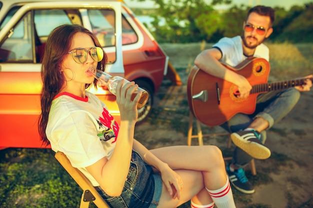 Paar sitzt und ruht sich am strand aus und spielt gitarre an einem sommertag in der nähe des flusses. liebe, glückliche familie, urlaub, reisen, sommerkonzept. Kostenlose Fotos