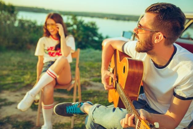 Paar sitzt und ruht sich am strand aus und spielt gitarre an einem sommertag in der nähe des flusses. Kostenlose Fotos