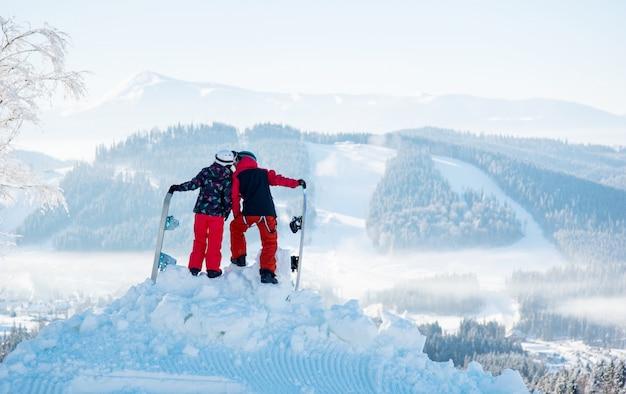 Paar snowboarder, die sich auf dem berg gegen schneebedeckte wälder und hügel im winterskigebiet küssen. rückansicht Premium Fotos