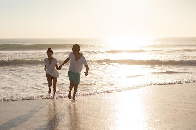 Paar spaß zusammen am strand Kostenlose Fotos