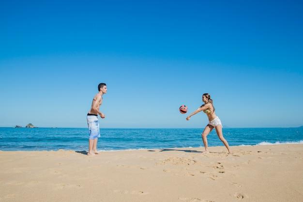 Paar spielt beach-volleyball an der küste Kostenlose Fotos