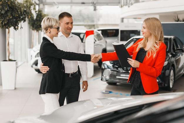 Paar treffen mit autohändler für den kauf des autos. Premium Fotos