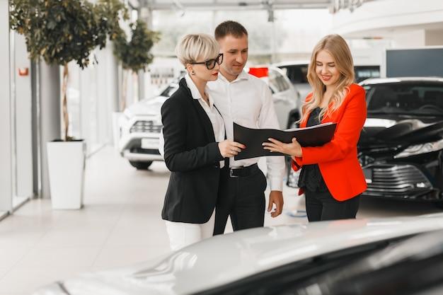 Paar treffen mit dem händler für die auswahl und den kauf des autos. Premium Fotos