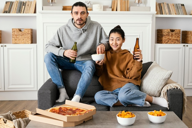 Paar trinkt bier und isst snacks drinnen Kostenlose Fotos
